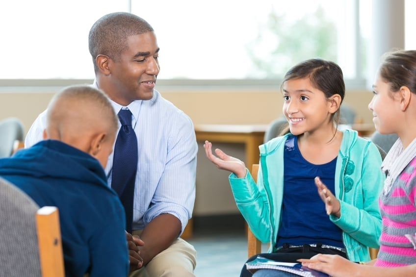Diverse group of elementary age little girls and little boys are sitting in circle with mid adult African American male counselor or therapist. Mental health professional is leading children's group therapy session. Children are smiling and talking expressively.