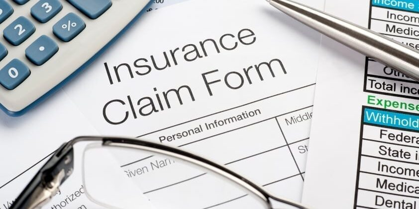 Close up of Insurance Claim Form with pen and calculator