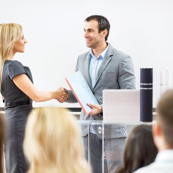 Group of people on a seminar. Focus is on business woman receiving a certificate from a lecturer.