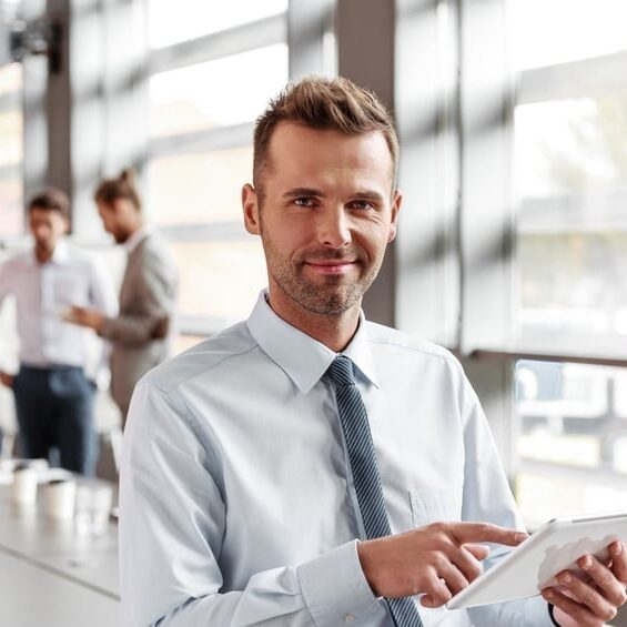 Portrait of friendly businessman wearing shirt and tie sitting in the board room, holding a digital tablet in hand and smiling at camera. Coworkers in the background.